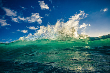 Sea water in sunlight rising green blue wave