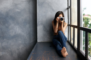 Picture of talented young unrecognizable brunette woman photograpther in jeans holding photo camera taking pictures or making setting, sitting barefooted on windowsill by large panoramic window