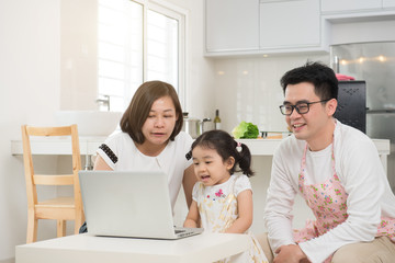 asian mother surfing internet with daughter while father cooking