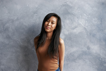 Indoor portrait of amazing charming young Asian female with long black hair, smiling shyly with arms behind her back, posing against blank studio wall background with copy space for your content