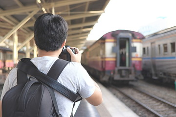 Back view of photographer taking a picture in train station. Selective focus and shallow depth of field.
