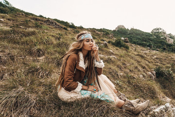 beautiful young boho girl in jacket sitting on a field