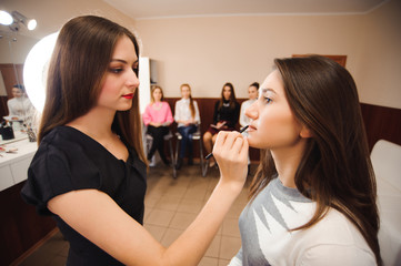 Make up artist teacher explaining l her student basic knowledge of how to apply make up properly on a brunette model girl.