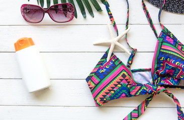 Summer Fashion woman swimsuit Bikini, camera, fish star, sunblock, sun glasses, hat on white wood. Travel in the holiday.  Summer Concept.