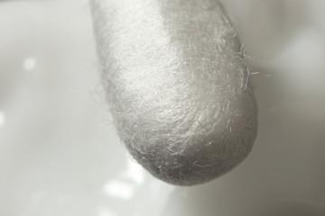 Cotton swab against a white cream