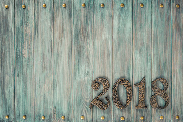 Metal forged 2018 date on vintage old mint green painted wooden wall planks texture background. Retro style filtered photo