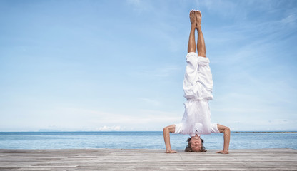 Young man doing yoga exercise - headstand, on a beautiful tropical beach