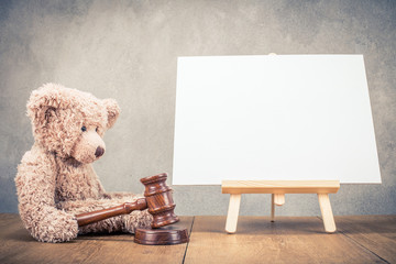 Teddy bear toy with auction gavel and easel for painting with canvas blank front concrete wall background. Retro instagram old style filtered photo