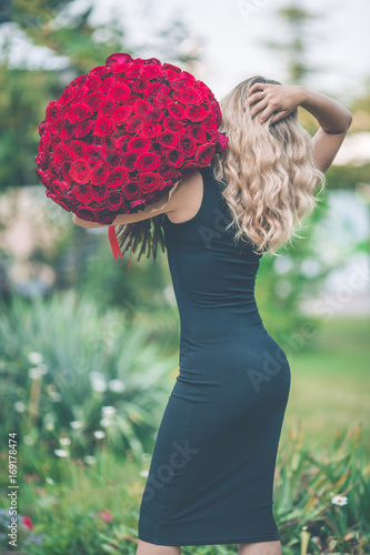 863b7df5a64 Back view of elegant beautiful woman is wearing black fashion dress on  green lawn with big