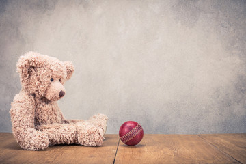 Retro Teddy Bear sitting alone and leather toy ball front old concrete wall background. Vintage instagram style filtered photo