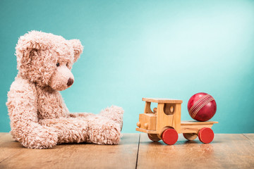 Retro Teddy Bear sitting alone with old wooden truck and leather toy ball front gradient aquamarine wall background. Vintage instagram style filtered photo