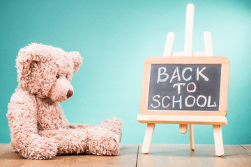 Retro Teddy Bear toy and Back to School written on a blackboard front gradient aquamarine wall background. Vintage instagram style filtered photo