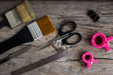 paint brushes, scissors and clamps on the wooden table