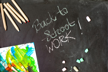 Back to school (work) composition and a writing on a black chalkboard background. Top view to items: color pencils, chalk, paint brushes.