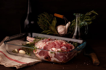 Fresh raw lamb leg ready for roasting with garlic and herbs