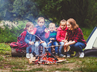Happy tourist family on journey hike. mother and children fry sausages on bonfire near tent