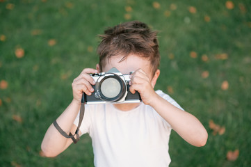 kid taking a picture using film camera