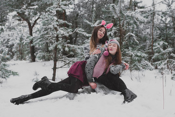 Close up fashion portrait of two sisters hugs and having fun winter time,wearing pink hats, rabbit ears and sweater,best friends couple outdoors, snowy weather