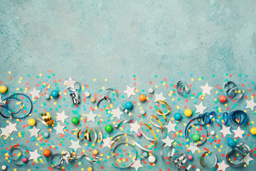 Holiday background decorated colorful confetti, star, candy and streamer on blue vintage table top view. Flat lay style. Festive border with copy space.