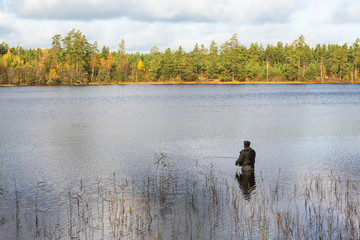 Fly fisherman standing in lake and fishing