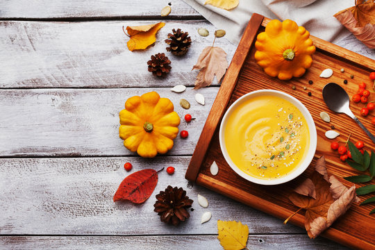 Wooden tray with hot autumn pumpkin soup decorated sesame seeds and thyme in white bowl on rustic vintage table top view. Cozy lifestyle shot for halloween menu.