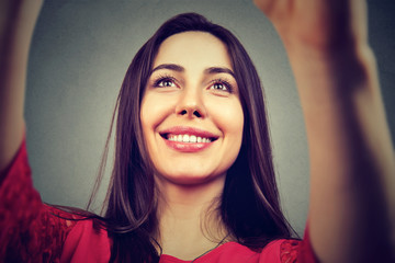 Closeup of young woman taking selfie isolated on gray background