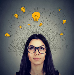 Serious woman in glasses with many ideas light bulbs above head looking up