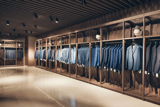 Interior of the business suit shop. Strict premium expensive suits hang in a row on hangers in large quantities