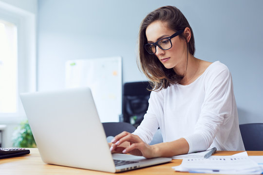 Concentraed young beautiful businesswoman working on laptop in bright modern office