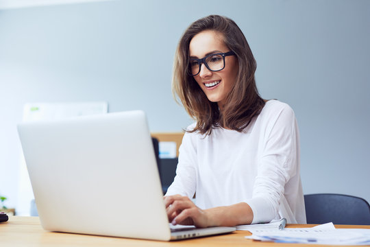 Front view of attractive lady working on laptop and smiling in modern home office