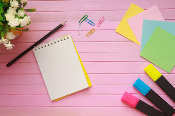 Top view of blank notebook page on pastel colored background office desk with different objects. Minimal flat lay style