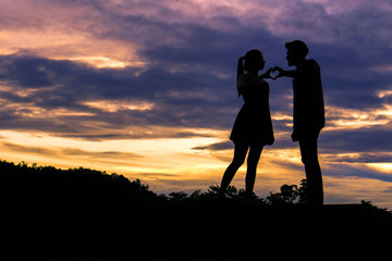 Silhouette couple in love fingers a heart shape as a symbol of love on beautiful sunset background , valentine concept