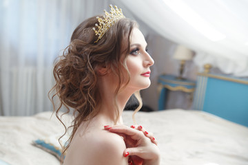 Sweet bride in profile with a crown on an airy voluminous hair.