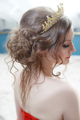 A beautiful bride in profile with a crown on an air hairstyle with strands falling on her shoulders.
