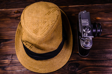 Old rangefinder camera and hat on a wooden table. Top view