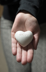 Woman hold in hands heart. Text hope