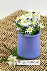 Happy Birthday card with white daisy flowers in blue porcelain vase on wicker surface
