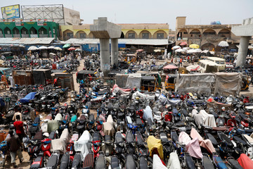 Motorcycles are parked near an unfinished bridge in the old Fagge district in Kano