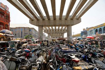 Motorcycles are parked under an unfinished bridge in the old Fagge district in Kano