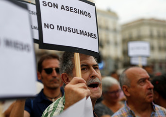 People hold signs as they take part in a march of unity after the attacks last week, in Madrid