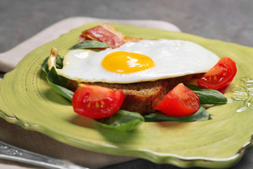 Delicious over easy egg with bread, bacon and tomatoes on plate, closeup