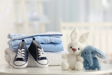 Cute knitted toys and baby clothes on table