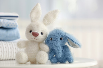 Cute knitted toys on table