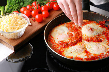 Woman cooking eggs in purgatory on stove