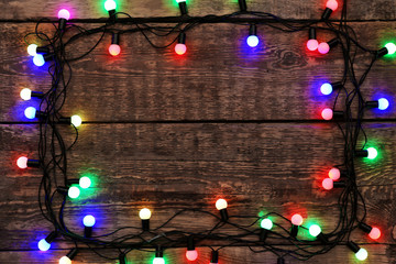 Frame of Christmas lights glowing on wooden background Wall mural