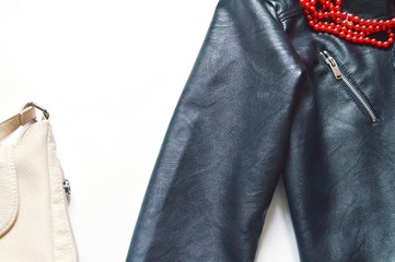Flat lay women's clothes/ Stylish female outfit for autumn season. Beige handbag, black biker jacket and red beads. Women's clothes flat lay photography for fashion blog. Free space for text