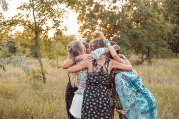 Girls stand in a circle embracing each other