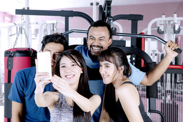 Diverse people taking selfie in the fitness center