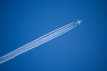 A jet plane flying overhead diagonally with condensation trail. Wall mural