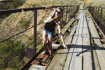 Beautiful young girl falls through the old rustic bridge. Actively shakes hands. Anxious and frightened face